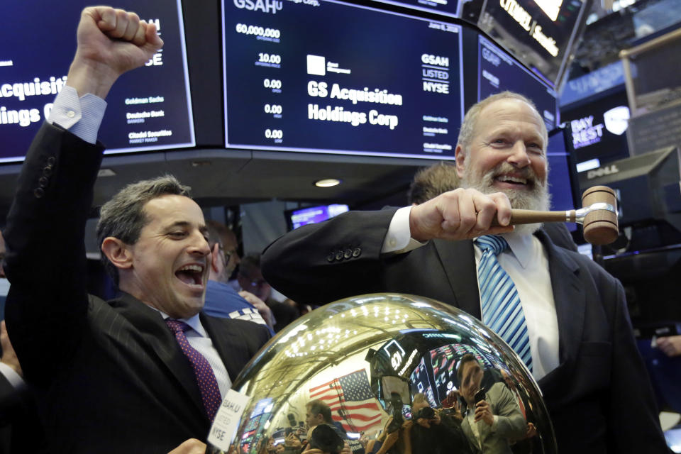 GS Acquisition Holdings Corp. CEO David Cote, right, rings a ceremonial bell on the floor of the New York Stock Exchange, as his company's IPO begins trading, Friday, June 8, 2018. At left is NYSE Vice President Chris Taylor. (AP Photo/Richard Drew)