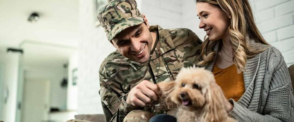 Young happy military officer having fun with his wife and dog after coming home from an assignment.