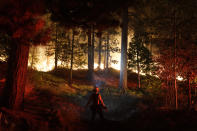 A firefighter monitors the Caldor Fire burning near homes in South Lake Tahoe, Calif., Monday, Aug. 30, 2021. As the winds returned, the Caldor Fire roared over the Sierra crest and bore down on the southern end of Lake Tahoe. (AP Photo/Jae C. Hong)