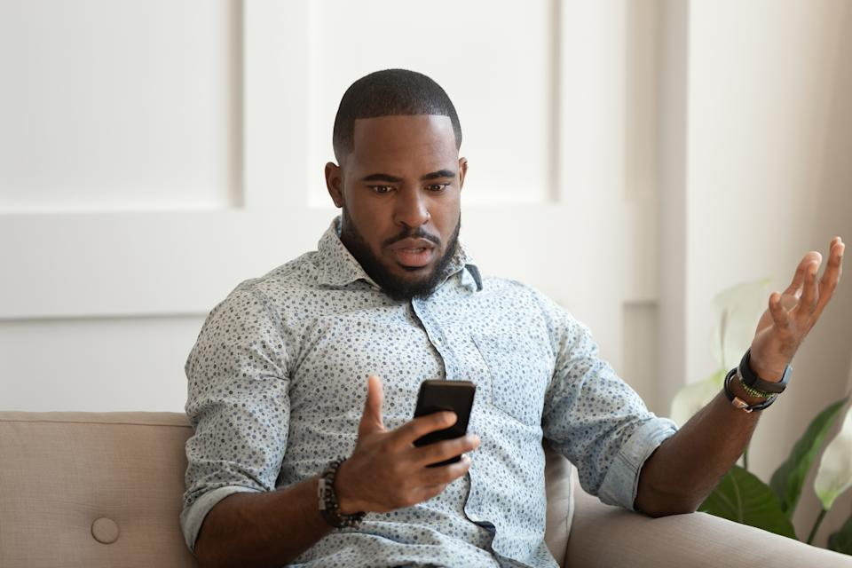 Man sitting on sofa holds cellphone read e-mail sms feels shocked received terrified news, guy looks at online calendar forgot missed important meeting, phone crash problems concept