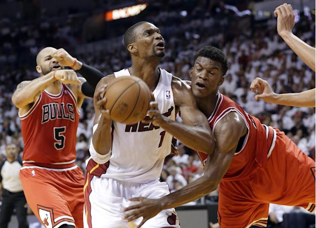 Miami Heat's Chris Bosh (1) drives to the basket as Chicago Bulls' Jimmy Butler, right, defends during the first half of Game 5 of an NBA basketball Eastern Conference semifinal, Wednesday, May 15, 2013 in Miami. At left is Bulls' Carlos Boozer. (AP Photo/Wilfredo Lee)
