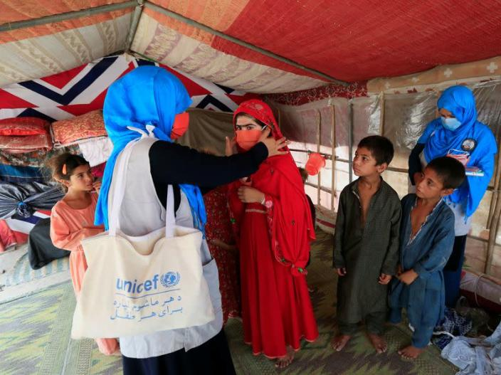 FILE PHOTO: A UNICEF worker helps an internally displaced girl put on a face mask at a makeshift camp, amid the coronavirus disease (COVID-19) outbreak, in Jalalabad