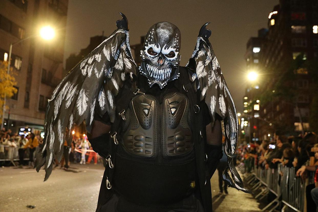 A reveler wearing a dark costume with wings marches in the Village Halloween Parade in New York City. (Photo: Gordon Donovan/Yahoo News)