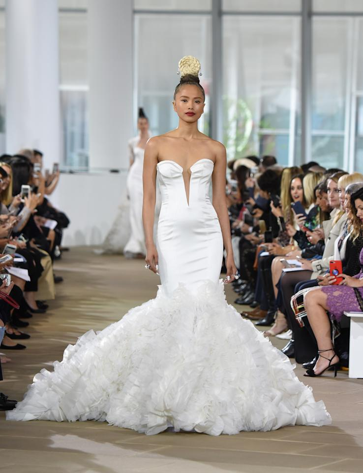 <p>Guests won't forget your wedding day if you're wearing this beautiful, satin mermaid gown. With its glove-like fit and beautifully ruffled skirt, we're betting your husband-to-be will remember this dress forever, too.</p>
