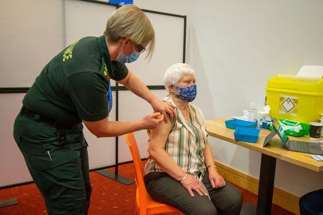 An elderly woman receives an injection of a Covid-19 vaccine at a NHS vaccination centre that has been set up at the Life Science Centre.