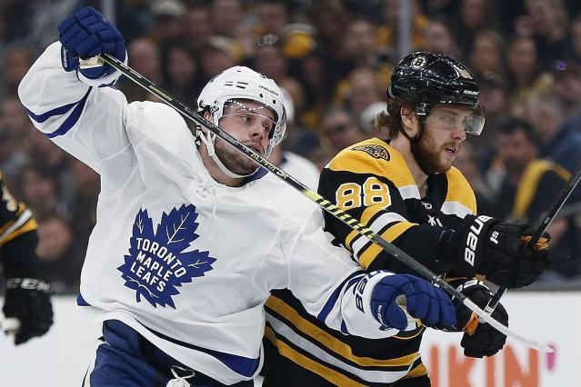 Boston Bruins' David Pastrnak (88) defends against Toronto Maple Leafs' Auston Matthews during the first period in Game 5 of an NHL hockey first-round playoff series in Boston, Friday, April 19, 2019. (AP Photo/Michael Dwyer)