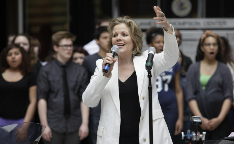 In this March 19, 2012 photo, famed soprano Renee Fleming performs with a choir of dozens of high school students in the rotunda of the State of Illinois building, the James R. Thompson Center, in Chicago. For the past school year the opera singer has been mentoring teenaged vocal students in Chicago as part of her role as creative consultant at the Lyric Opera of Chicago.(AP Photo/Kiichiro Sato)