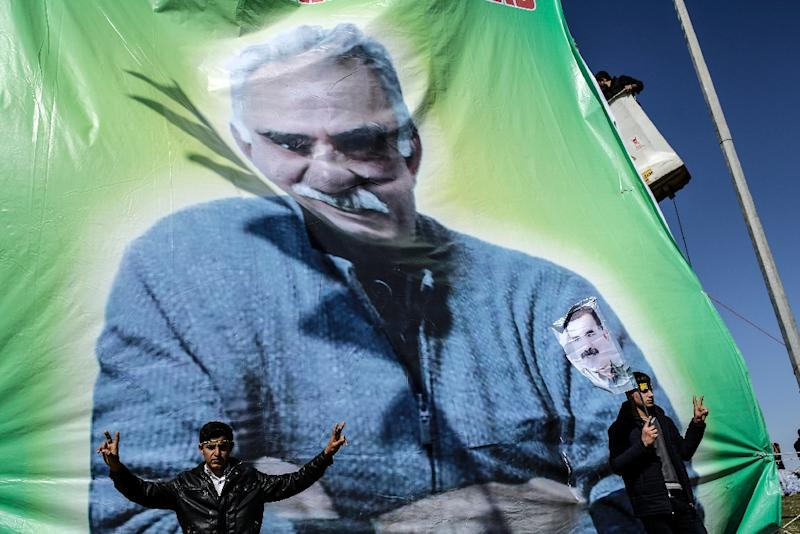 Men flash the 'V for Victory' sign near a banner bearing a portrait of jailed Kurdish leader Abdullah Ocalan as they celebrate Newroz, which marks the arrival of spring and the new year, in the Turkish town of Suruc on March 17, 2015 (AFP Photo/Yasin Akgul)