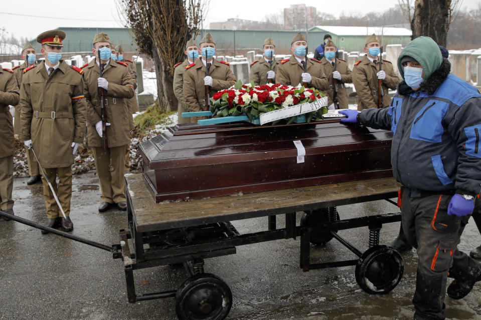 """FILE - In this Jan, 11, 2021 file photo, the coffin of Iancu Tucarman is is transported on a cart, past an honor guard, at a Jewish cemetery for burial after dying of COVID-19 in Bucharest, Romania, Monday, Jan. 11, 2021. After the European Union passed the death toll of half a million citizens lost to the coronavirus on Wednesday, Feb. 10, 2021, the EU Commission chief said that stalling rollout of the vaccines could be partly blamed on the bloc being over-optimistic, over-confident and plainly """"too late."""" (AP Photo/Vadim Ghirda, File)"""