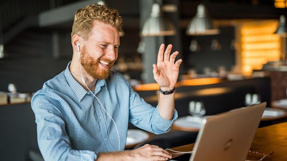 Happy young businessman waving to an online client.