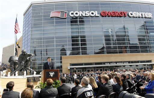 Pittsburgh Penguins Hall of Fame center Mario Lemieux, center, addresses the crowd gathered outside the NHL hockey team's arena after the statue of him at left was unveiled on Wednesday, March 7, 2012 in Pittsburgh. (AP Photo/Keith Srakocic)
