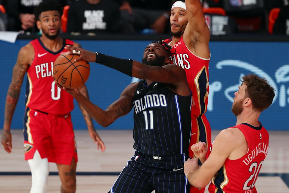 James Ennis III #11 of the Orlando Magic is fouled by Nicolo Melli #20 of the New Orleans Pelicans as he shoots against Josh Hart #3 during the second half of an NBA basketball game at the ESPN Wide World Of Sports Complex.