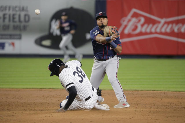 New York Yankees' Cameron Maybin (38) slides into second base as Minnesota Twins second baseman Luis Arraez (2) makes the throw to first for a double play during the sixth inning of Game 2 of an American League Division Series baseball game, Saturday, Oct. 5, 2019, in New York. (AP Photo/Seth Wenig)