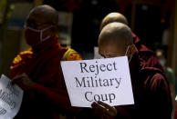 Buddhist monks display placrds during a protest march against the military coup in Yangon, Myanmar Tuesday, Feb. 16, 2021. In the month since Feb. 1 coup, the mass protests occurring each day are a sharp reminder of the long and bloody struggle for democracy in a country where the military ruled directly for more than five decades. (AP Photo)