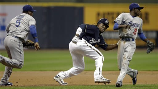 Los Angeles Dodgers' Dee Gordon (9) watches as Juan Uribe tags out Milwaukee Brewers' Rickie Weeks after Weeks got caught in a rundown during the first inning of a baseball game Tuesday, April 17, 2012, in Milwaukee. (AP Photo/Morry Gash)