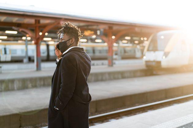 Handsome confident businessman on his way home from work. He is standing on the train station platform at sunset, waiting for his train. (Photo: luza studios via Getty Images)