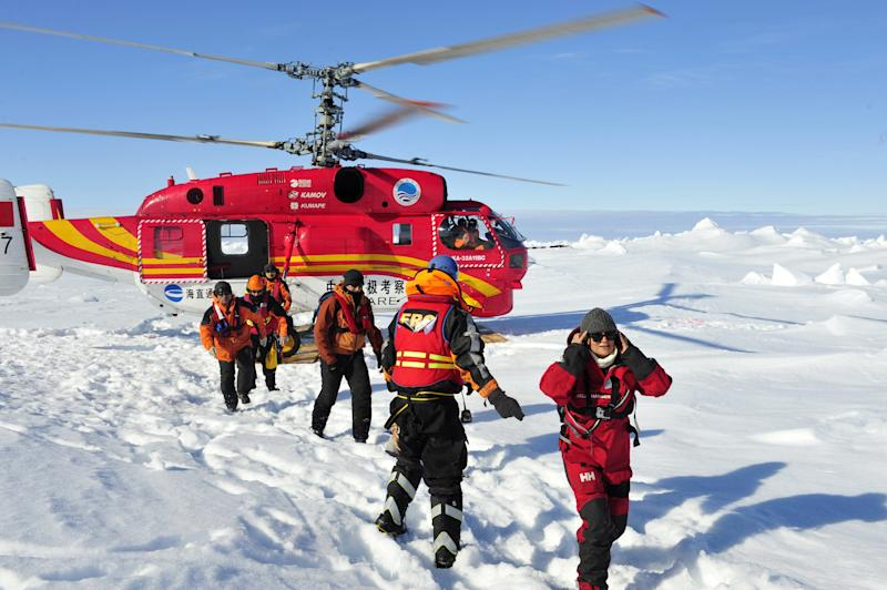 In this photo provided by China's Xinhua News Agency, the first group of passengers who were aboard the trapped Russian vessel MV Akademik Shokalskiy arrive at a safe surface off the Antarctic, Thursday, Jan. 2, 2014. The helicopter rescued all 52 passengers from the research ship that has been trapped in Antarctic ice, 1,500 nautical miles south of Hobart, Australia, since Christmas Eve after weather conditions finally cleared enough for the operation Thursday. (AP Photo/Xinhua, Zhang Jiansong) NO SALES