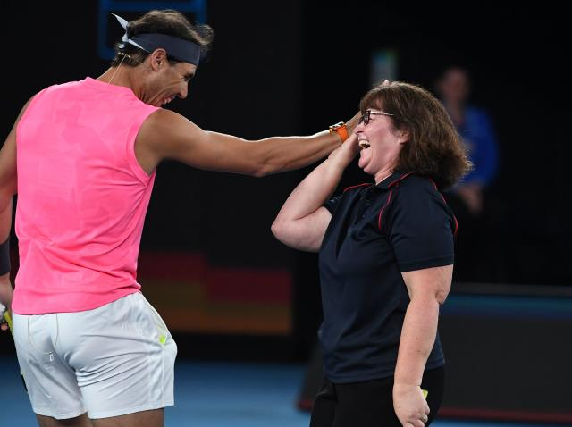 Rafael Nadal of Spain (L) high-fives local firefighter Deb Borg (R) as he and the world's top players play in the Rally for Relief charity tennis match in support of the victims of the Australian bushfires, in Melbourne of January 15, 2020, ahead of the Australian Open tennis tournament. (Photo by WILLIAM WEST / AFP) / -- IMAGE RESTRICTED TO EDITORIAL USE - STRICTLY NO COMMERCIAL USE -- (Photo by WILLIAM WEST/AFP via Getty Images)