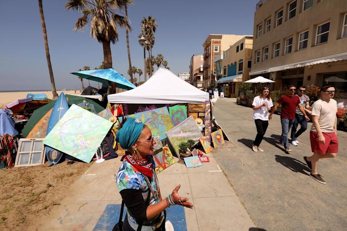 A woman stands by a tent with artwork as people walk by