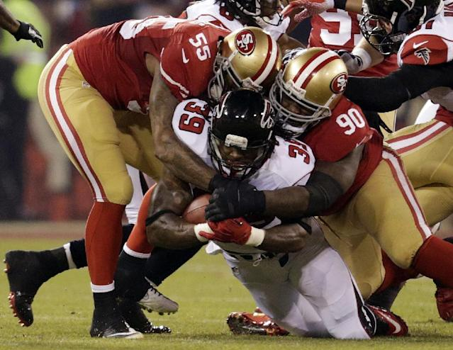 Atlanta Falcons running back Steven Jackson (39) is tackled by San Francisco 49ers' Ahmad Brooks (55) and Glenn Dorsey during the first half of an NFL football game in San Francisco, Monday, Dec. 23, 2013. (AP Photo/Tony Avelar)