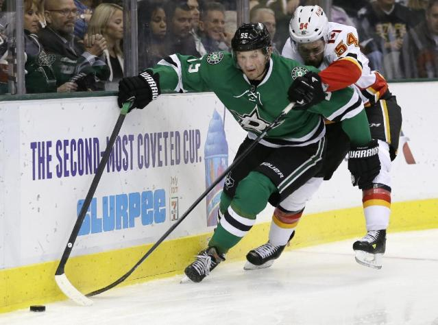 Dallas Stars defenseman Sergei Gonchar (55), of Russia, attempts to maintain control of the puck behind the net as Calgary Flames' David Jones (54) pressures in the second period of an NHL hockey game on Thursday, Oct. 24, 2013, in Dallas. (AP Photo/Tony Gutierrez)