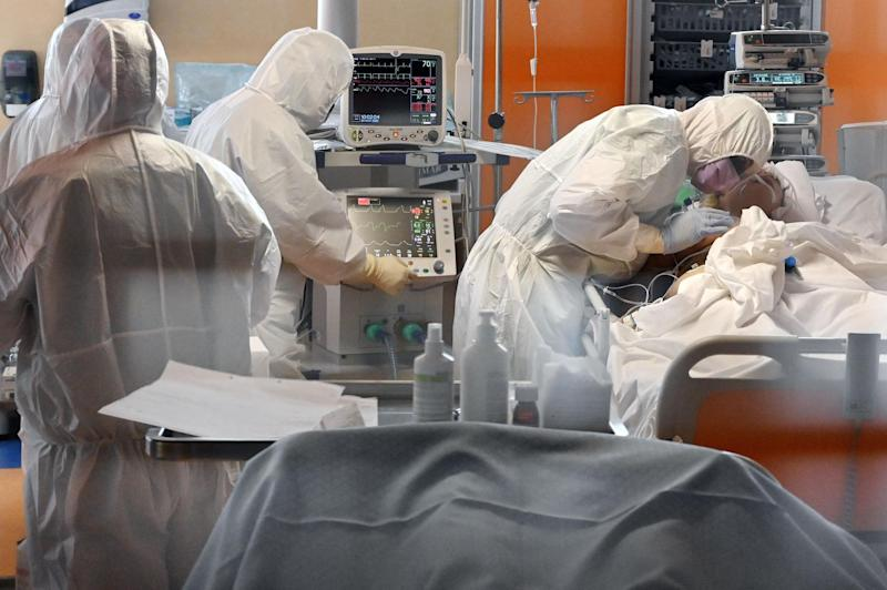 A medical worker in protective gear tends to a Covid-19 patient at a hospital in Rome, during the country's lockdown: AFP via Getty Images
