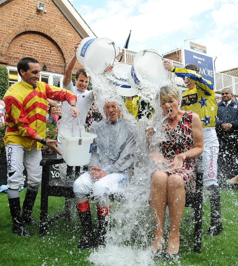 Jockey Frankie Dettori and television presenter Clare Balding take part in the 'Ice Bucket Challenge' in aid of motor neurone disease on Coolmore Nunthorpe Stakes Day during Day Three of the 2014 Welcome To Yorkshire Ebor Festival at York Racecourse, York.
