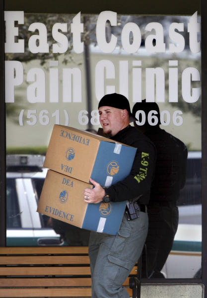 FILE - In this March 2010 file photo, Law enforcement agents carry out boxes of evidence gathered from the East Coast Pain Clinic  West Palm Beach, Fla. Florida's 'pill mills' were a gateway to the nation's opioid crisis, feeding addiction and overdoses in Appalachia and other states. They exploded across Florida in the early 2000s and operated for years with little oversight. The release this week of July 19, 2019,  of a trove of federal data showing the distribution of opioids across the U.S. put the spotlight again on Florida's notorious 'pill mills,' which provided the seeds of an epidemic that continues to cost tens of thousands of lives each year.  (Bill Ingram/Palm Beach Post via AP)/