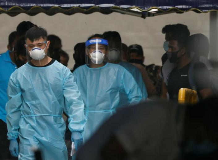 Personnel in protective garment usher a group of migrant workers at Westlite Woodlands dormitory in Singapore