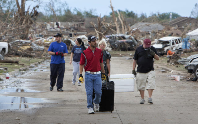 Residents remove their belongings from a residential area in Moore, Oklahoma May 21, 2013 after a massive tornado struck the area May 20. Emergency workers pulled more than 100 survivors from the rubble of homes, schools and a hospital in an Oklahoma town hit by a powerful tornado May 20, and officials lowered the death toll from the storm to 24, including nine children. REUTERS/Richard Rowe (UNITED STATES - Tags: DISASTER ENVIRONMENT) - RTXZVIZ
