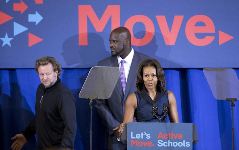 First lady Michelle Obama, right, is joined by Shaquille O'Neal, and North America Reebok President Uli Becker, left, during a visit to Orr Elementary in Washington, Friday, Sept. 6, 2013, for a back to school event highlighting healthy changes in schools and across the country. (AP Photo/Manuel Balce Ceneta)