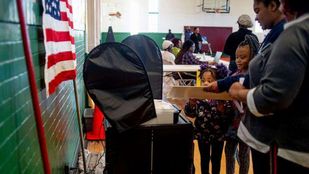 PHOTO: A pair of young girls help their mother submit her ballot at Haskell Community Center in Flint, Mich., March 10, 2020. (Jake May/The Flint Journal via AP)