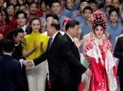 Macau Chief Executive Ho Iat-seng shakes hands with a performer next to Chinese President Xi Jinping on the stage during a cultural performance in Macau