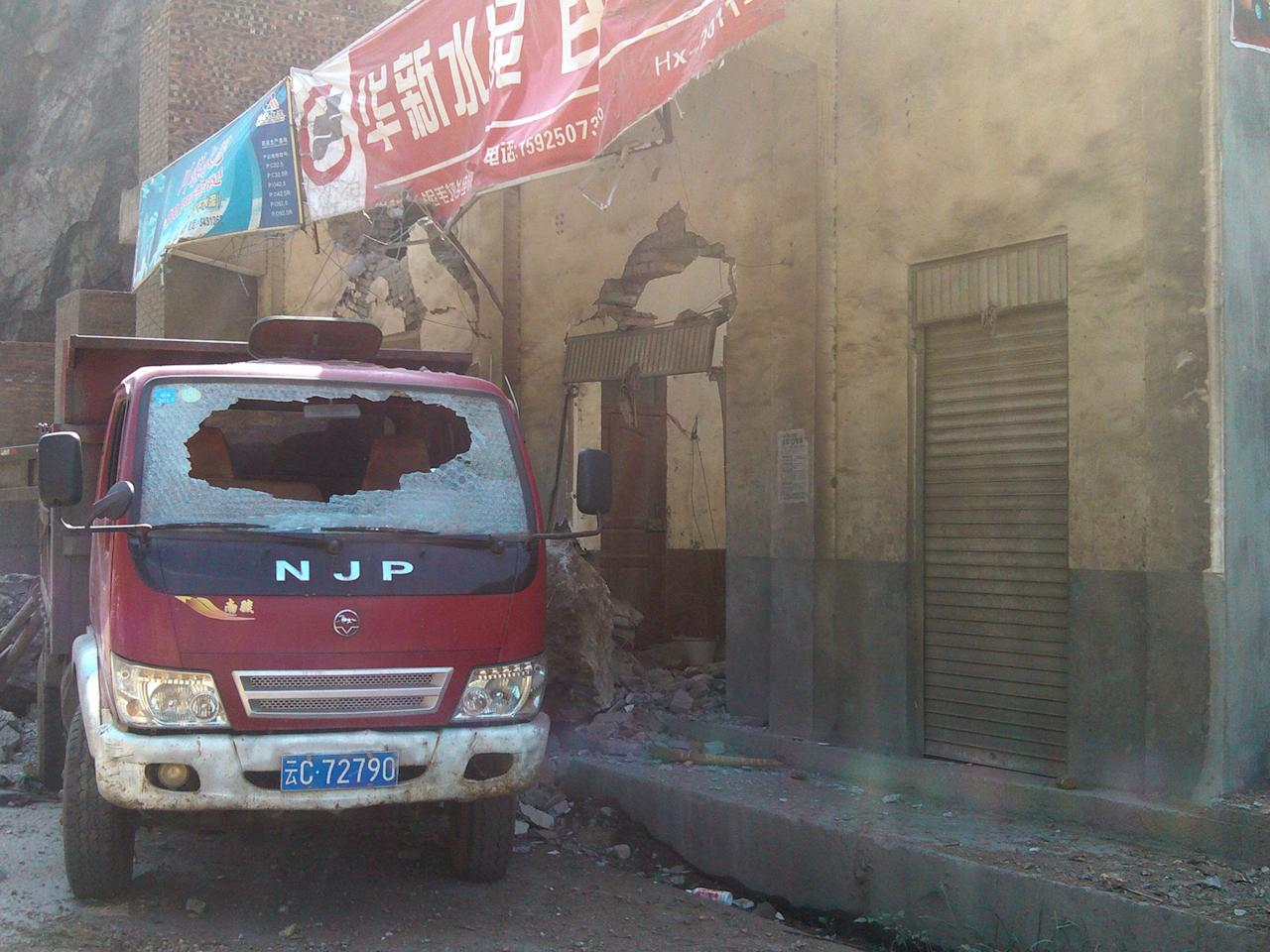 In this photo provided by Xinhua News Agency, a damaged truck parks by damaged houses in Luozehe Town, Yiliang County, southwest China's Yunnan Province, Sept. 7, 2012. A series of earthquakes collapsed houses and triggered landslides in a remote mountainous part of southwestern China on Friday, killing dozens of people with the toll expected to rise. Damage was preventing rescuers from reaching some outlying areas, and communications were disrupted. (AP Photo/Xinhua, Zhou Hongpeng)