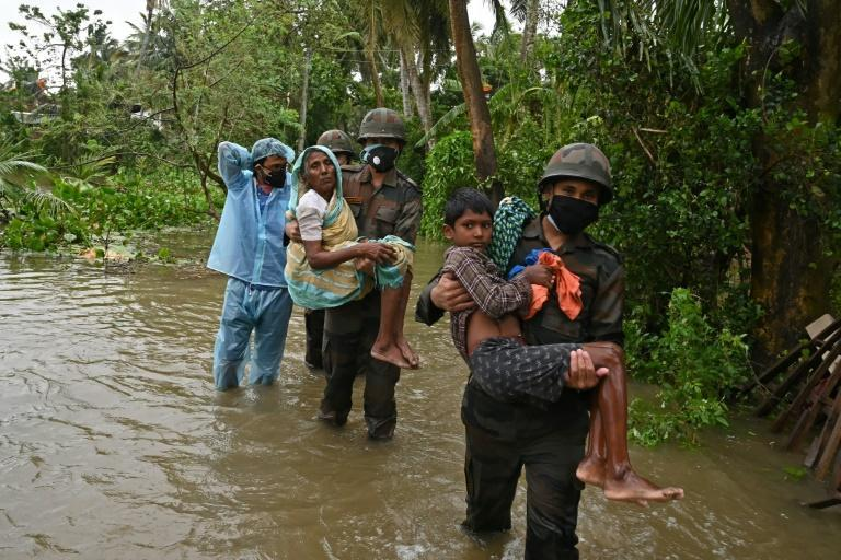 Indian army personnel wade through flooded village roads carrying people to safety as Cyclone Yaas batters the country