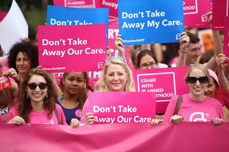 Participants hold pink Planned Parenthood banner and signs at a NYC demonstration. Photo by Andy Katz/Getty Images
