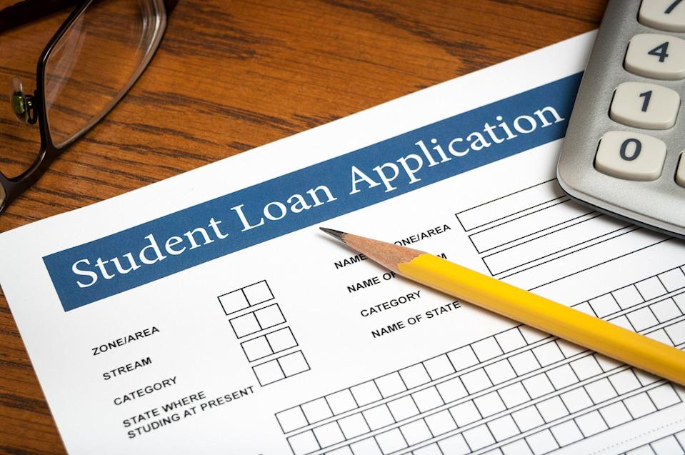 Pencil and calculator resting on student loan application