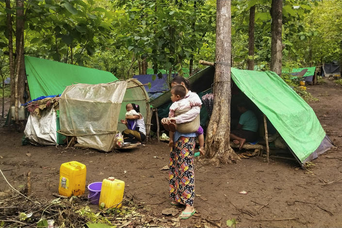 An internally displaced woman carries a child outside makeshift tents at Pu Phar Village, Demawso Township, Kayah State on Thursday June 17, 2021. A report on the situation in conflict-affected areas of Myanmar issued this week by the U.N.'s Office for the Coordination of Humanitarian Affairs says around 108,800 people from Kayah State were internally displaced following an escalation of hostilities between the government military and the local Karenni People's Defense Force militia since the coup Feb. 1, 2021. (AP Photo)