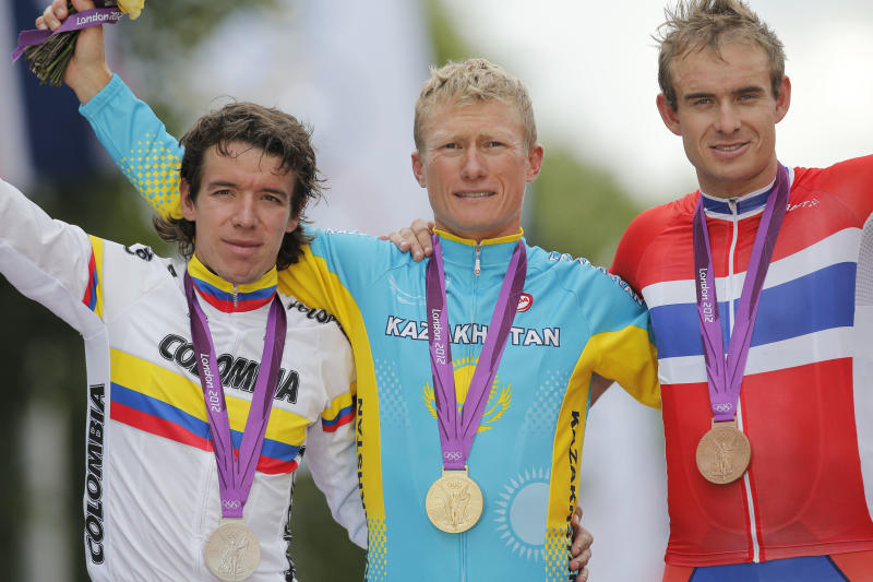 Kazakhstan's Alexandr Vinokourov center, poses for photographs with silver medalist Rigoberto Uran of Colombia, left, and bronze medalist Alexander Kristoff, right, after winning the Men's Road Cycling Race at the 2012 Summer Olympics, Saturday, July 28, 2012, in London. (AP Photo/Christophe Ena)