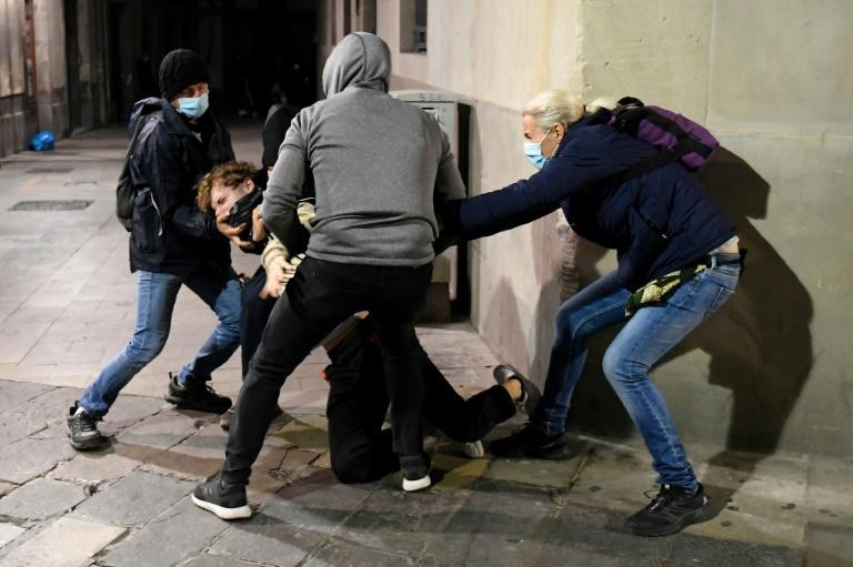 Catalan police officers in plain clothes arrest a protesters in Barcelona