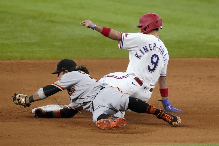 San Francisco Giants shortstop Brandon Crawford, left, is unable to tag Texas Rangers' Isiah Kiner-Falefa (9) who steals second in the ninth inning of a baseball game in Arlington, Texas, Wednesday, June 9, 2021. (AP Photo/Tony Gutierrez)