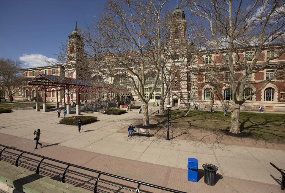 FILE - Tourists walk around the grounds at Ellis Island, on April 29, 2015, in New York. The location is featured in a collection of mini-essays by American writers published online by the Frommer's guidebook company about places they believe helped shape and define America. (AP Photo/Julie Jacobson, File)