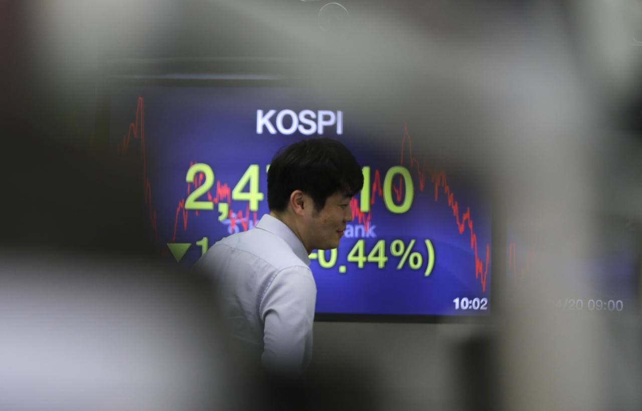 A currency trader walks by the screen showing the Korea Composite Stock Price Index (KOSPI) at the foreign exchange dealing room in Seoul, South Korea, Friday, April 20, 2018. Asian stock markets drifted mostly lower on Friday snapping two straight days of gains as Apple suppliers in the region weighed on the broader market. (AP Photo/Lee Jin-man)