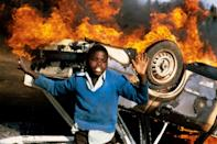 A South African boy dances on July 10, 1985 around the burning car of a suspected police informer who Tutu earlier saved from being thrown onto the fire (AFP/GIDEON MENDEL)