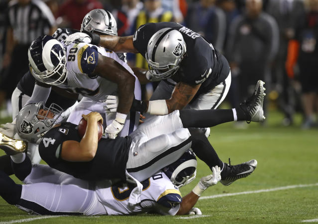 Oakland Raiders quarterback Derek Carr is brought down by Los Angeles Rams defensive tackle Michael Brockers (90) on Monday night. (AP)