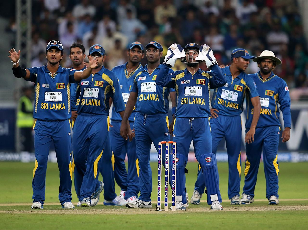 DUBAI, UNITED ARAB EMIRATES - DECEMBER 13:  Players of Sri Lanka wait for a pending run-out decision during the second Twenty20 International match between Pakistan and Sri Lanka at Dubai Sports City Cricket Stadium on December 13, 2013 in Dubai, United Arab Emirates.  (Photo by Francois Nel/Getty Images)