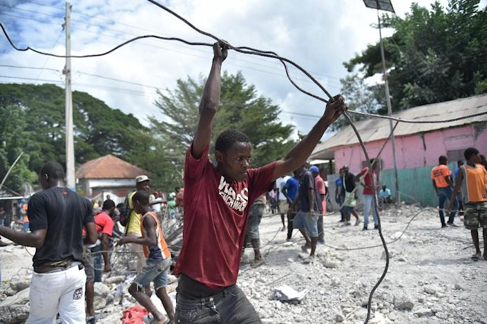 Local residents collected metal from the debris of a building in Gros-Morne, Haiti, flattened by an October 6 earthquake that killed at least 12 people and injured dozens (AFP Photo/HECTOR RETAMAL)