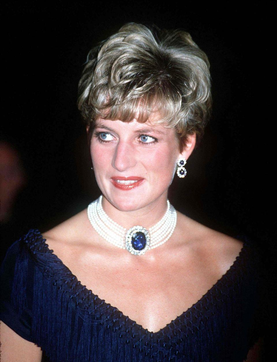 <p>In the early nineties, Princess Diana opted for a shorter fringe. Here, Diana chose to wear the Queen Mother's sapphire brooch as a necklace with co-ordinating earrings to a gala performance at the Royal Albert Hall.<br><em>[Photo: PA]</em> </p>