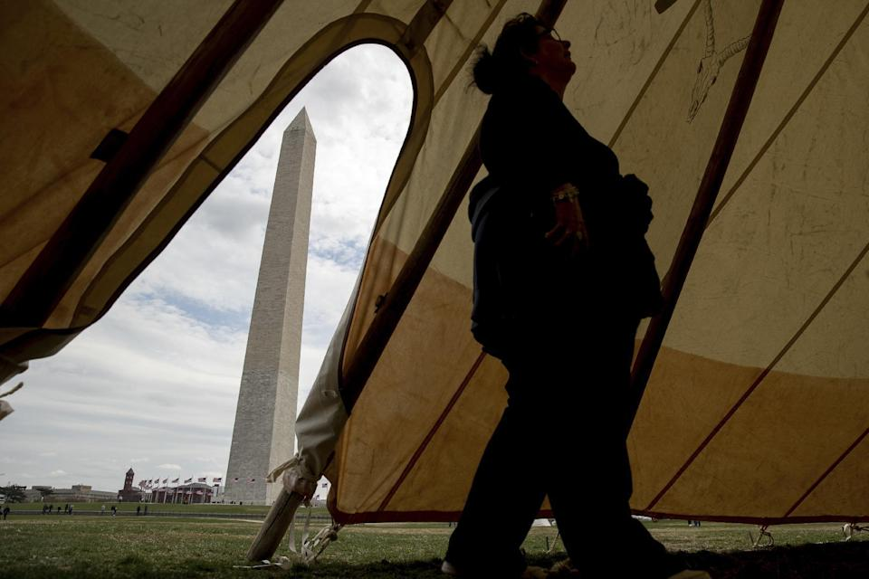 Patty Aitchison of Detroit walks into a teepee to speak with a group protesting the Dakota Access oil pipeline on the National Mall near the Washington Monument in Washington, Tuesday, March 7, 2017. A federal judge declined to temporarily stop construction of the final section of the disputed Dakota Access oil pipeline, clearing the way for oil to flow as soon as next week. (AP Photo/Andrew Harnik)
