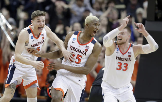 FILE - In this March 30, 2019, file photo, Virginia's Mamadi Diakite, center, reacts with teammates Kyle Guy and Jack Salt (33) after hitting a shot against Purdue to send the game into overtime in a regional final of the NCAA college basketball tournament in Louisville, Ky. Diakite was a huge part of the win, but he's still driven by The Loss. The 6-foot-9 redshirt senior says he will never forget, or cease to be driven by, Virginia's loss to UMBC as the first No. 1 seed in NCAA Tournament history to lose to a No. 16 seed. The defending national champions are young this season, but Diakite says they have some surprises in store. (AP Photo/Michael Conroy, File)